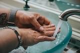 Hands under a running tap.