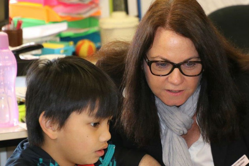 A female teacher wearing glasses helps a young boy on his lap top