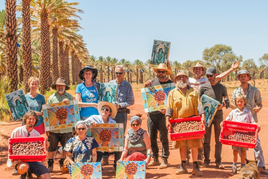 13 adults and one child stand holding boxes of dates harvested on a Northern Territory farm