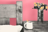Photo and illustration of bedside table with flowers and mug to depict the act of supporting a dying loved one.