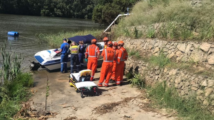 A small boat crashed into an embankment surrounded by SES and ambulance workers.