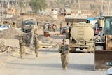 U.S. soldiers gather in the town of Gwer