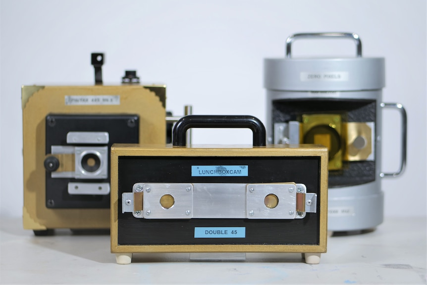 Three different pinhole cameras, with metal 'lunchbox camera' in front and cardboard version behind at left