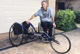 A man in a wheel chair sits next to his racing wheel chair.