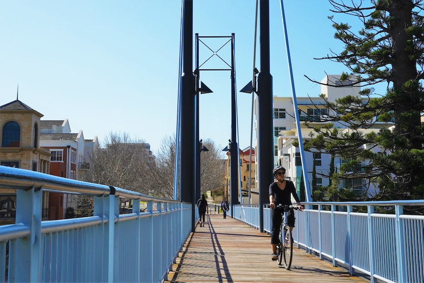 A woman rides her bike over bridge in East Perth