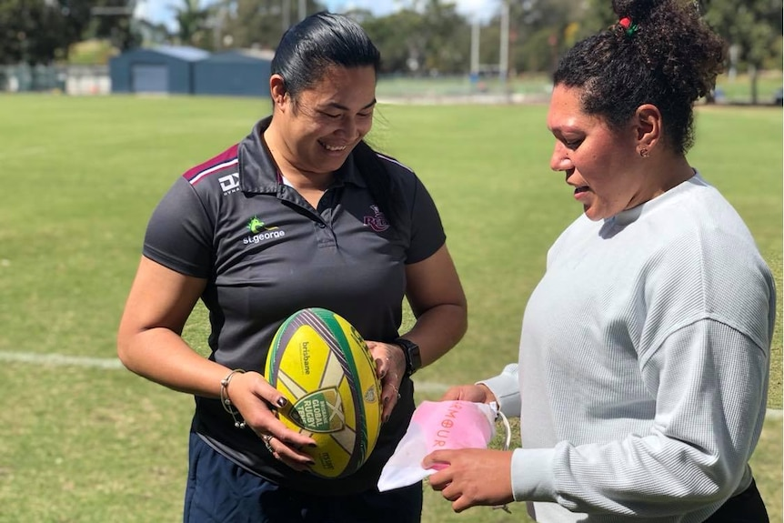 Alisi Qalo-Wilson (left) and Liz Patu (right).  Liz shows Alisi a package with a sports bra.