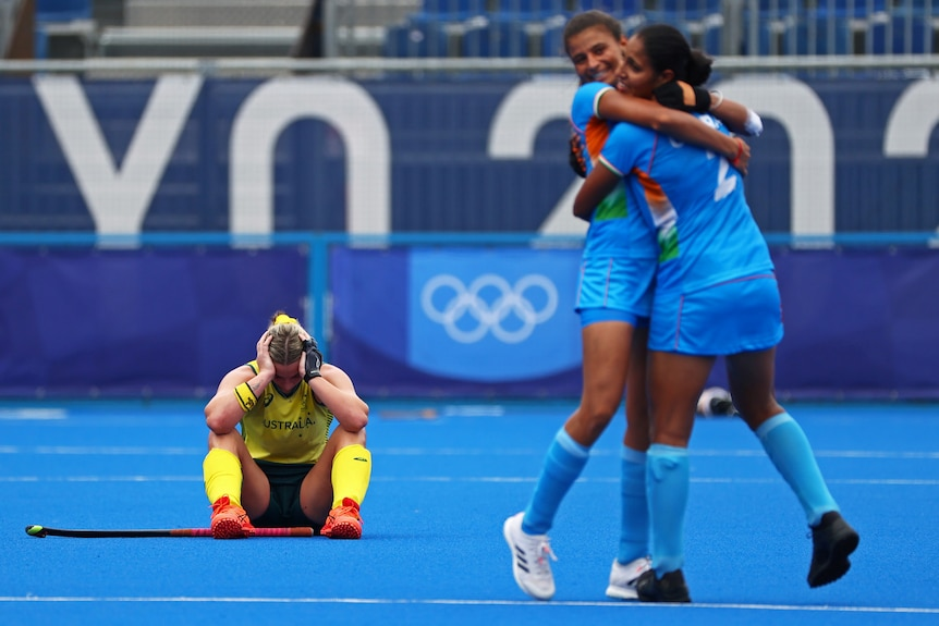 A group of Indian hockey players in blue celebrate as a single yellow player sits and looks sad in a hockey match.