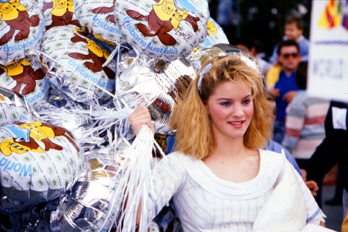 A woman holding balloons at Expo 88 in Brisbane