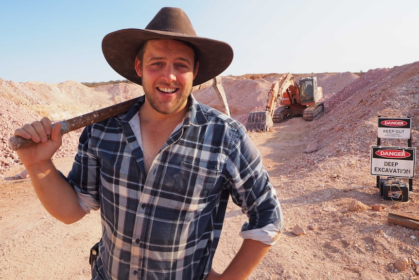 A man in a broad brown hat smiles as he holds a pick axe over his shoulder, standing in front of an excavator and dirt mounds