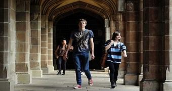 Students walking through a university corridor.