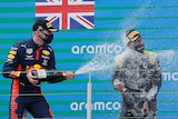 A mask-wearing Formula 1 driver flinches away as he is sprayed with champagne by another driver.