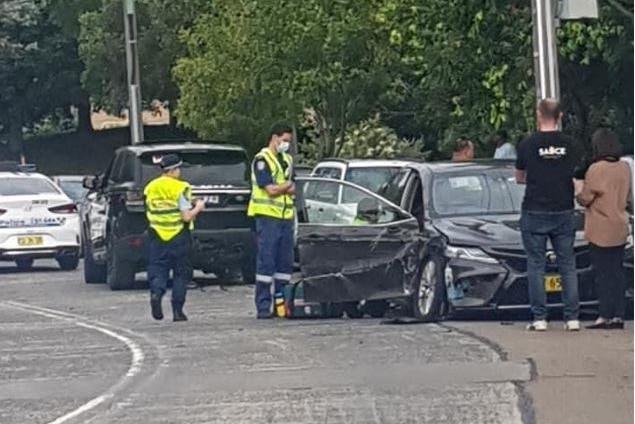 Police surround a black car that has been crushed in a car crash