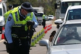 A policeman stands beside a car examining the driver's wallet.