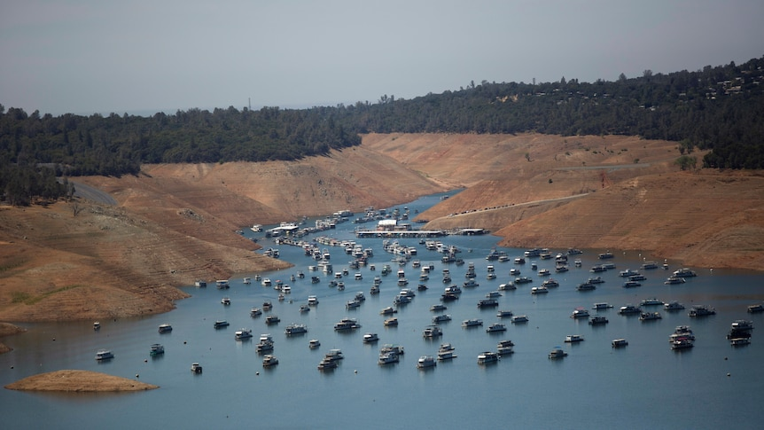 An aerial shot of a lake dotted with boats.