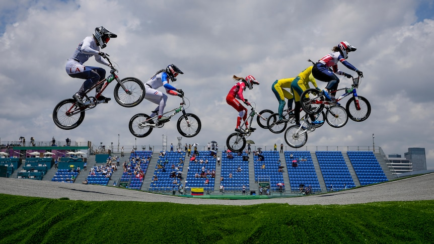 Six riders are high in the air as they go over a big jump in the BMX racing, with a stand in the background.