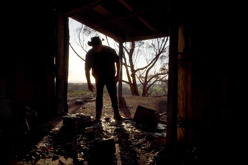 Barry Smith standing inside a room of his damaged property