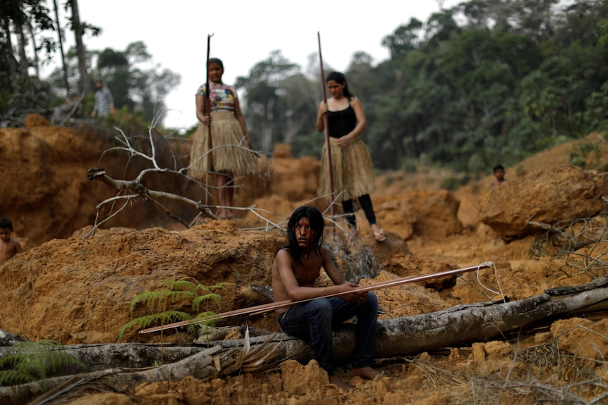 Indigenous people in Brazil sit in a deforested area of the Amazon rainforest on August 20, 2019.