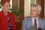 Pauline Hanson stands smiling beside Malcolm Roberts.