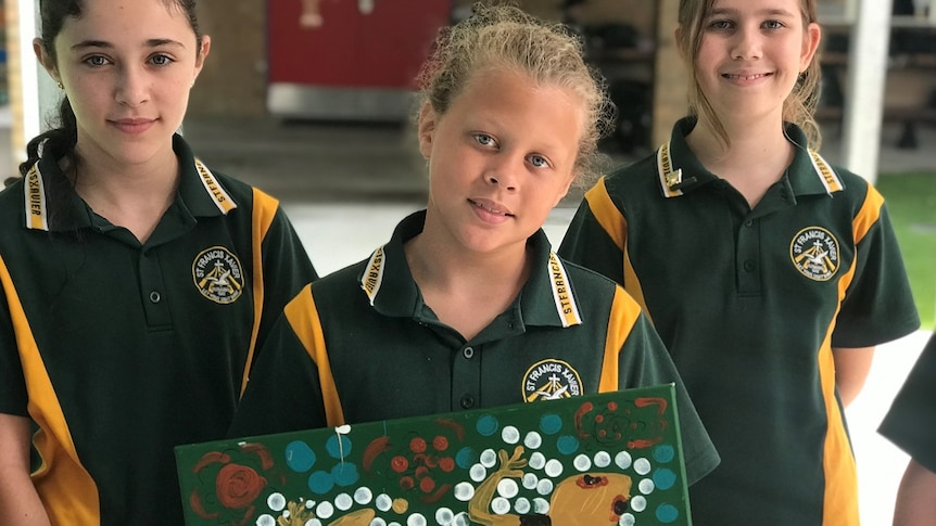 Two children in green and yellow in background, young boy with blond hair and blue eyes in foreground holding goanna painting.