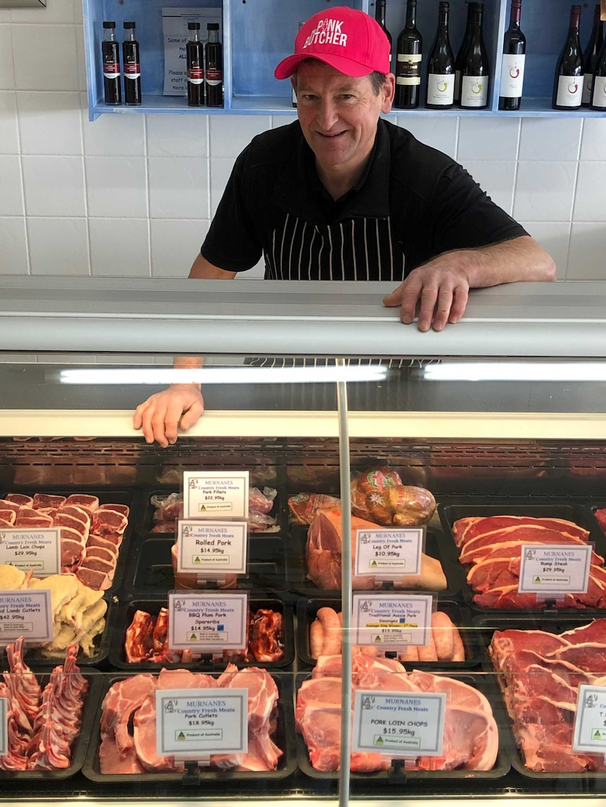 Butcher in his shop wearing a jaunty red cap and smiling over his chops.