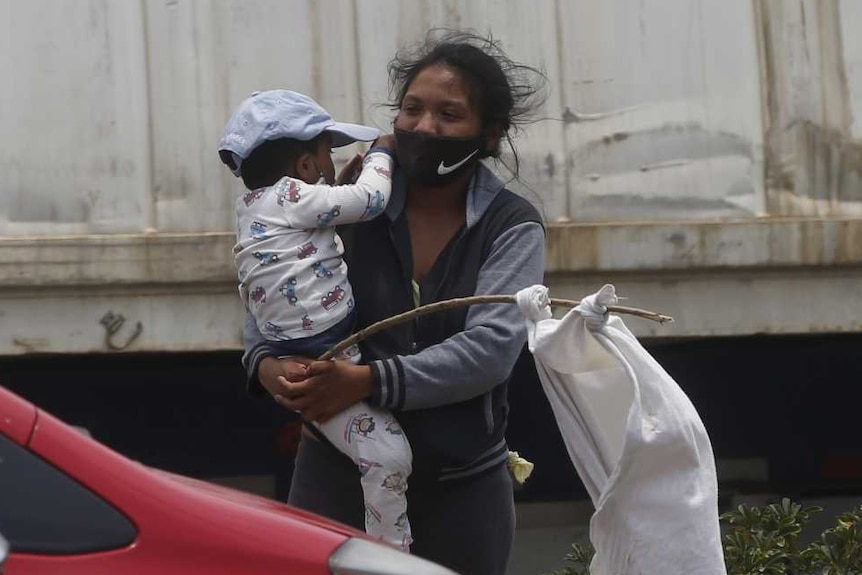 Leidy and her two-year-old son Leiton wave a white flag on la carretera al Pacifico in Villa Nueva, Guatemala, on 6 May 2020.