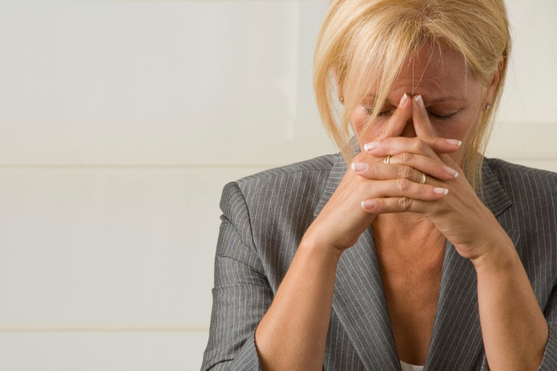 Woman with her head in her hands looking stressed.