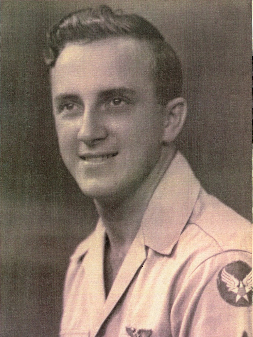 A black and white photo of a young man dressed in air force uniform smiling