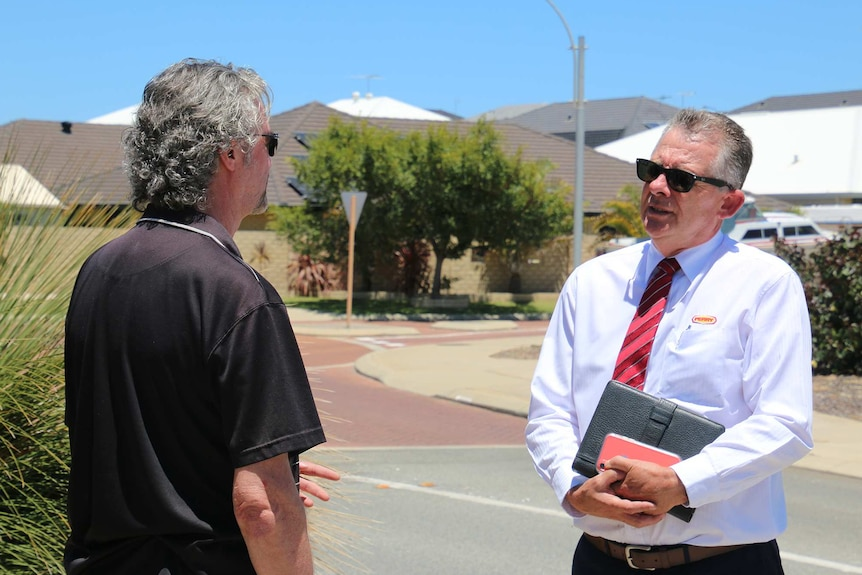 Two men, one a real estate agent, stand talking on a suburban street.