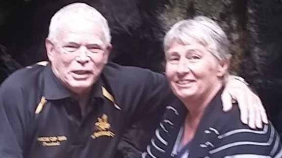An older man with his arm around his wife.