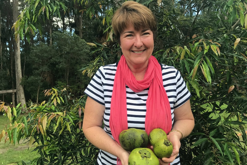 Helen Andrew holding black sapote fruit that Spare Harvest helped sell.