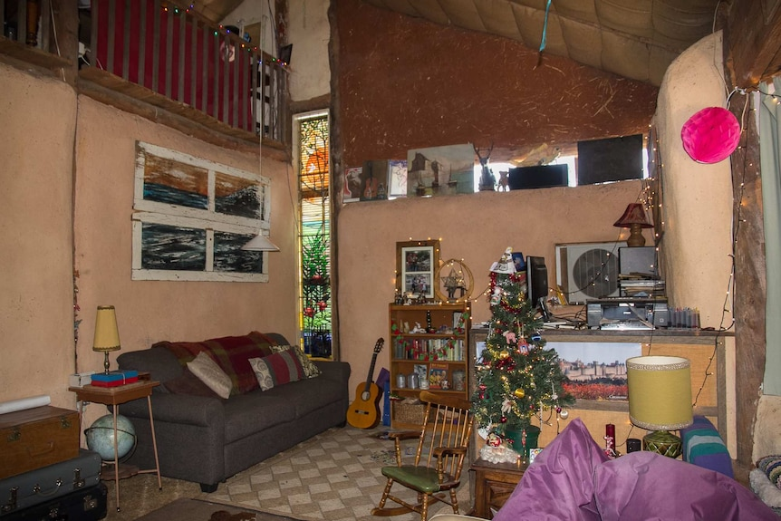 Inside of a lounge room of a straw bale house with exposed poles and straw