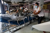 People wearing face masks move a gurney at a damaged hospital.