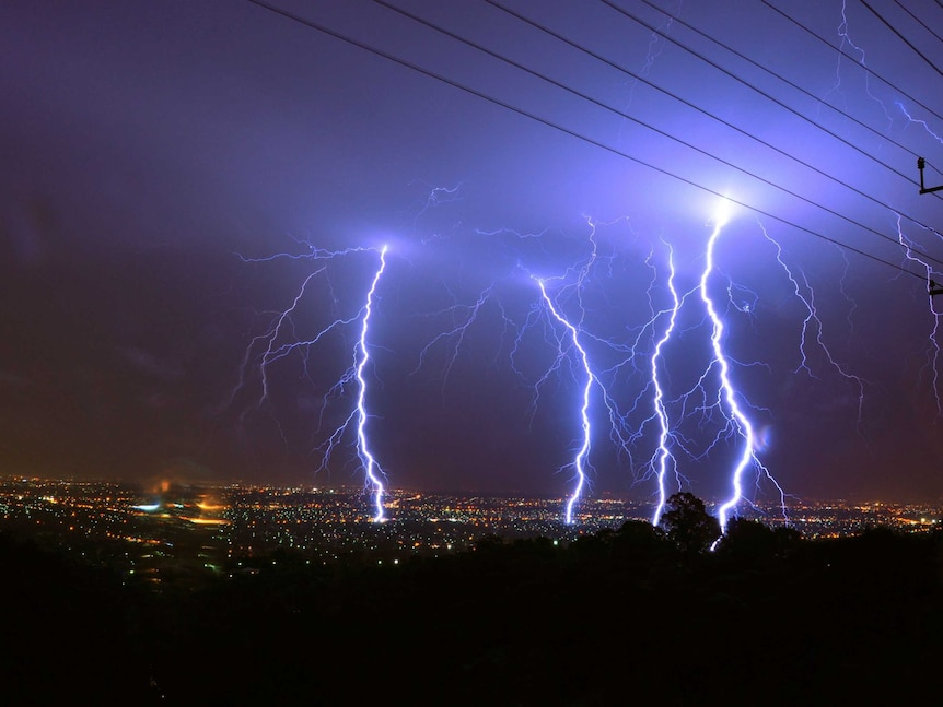 Four forks of lightning strike a city at night.