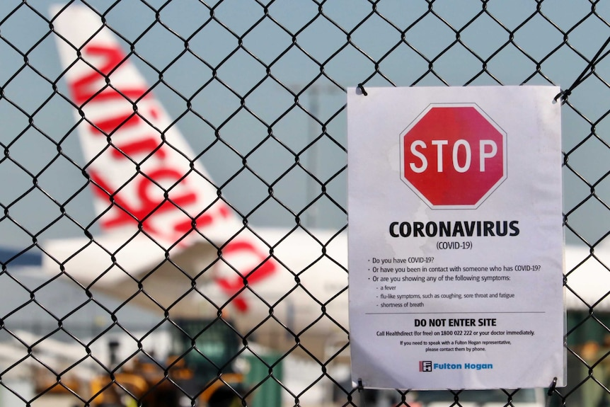 A coronavirus warning sign on a wire fence, in front of a Virgin plane