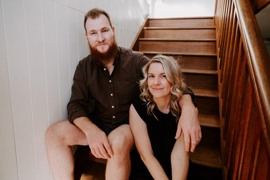 An image of Genevieve Worrell and Lachlan Mackintosh sitting together on stairs.