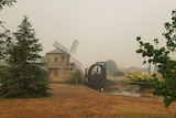 A rural property featuring a windmill, dam and water wheel.