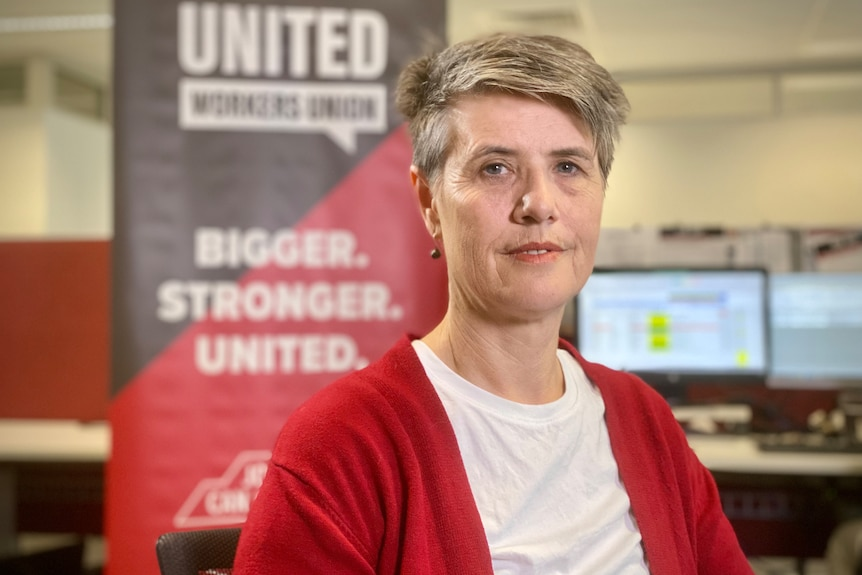 Carolyn Smith wearing a red cardigan in an office, in front of large black and red United Workers Union sign.