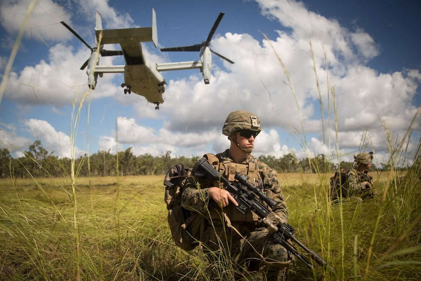 A soldier stands with a gun under a helicopter.