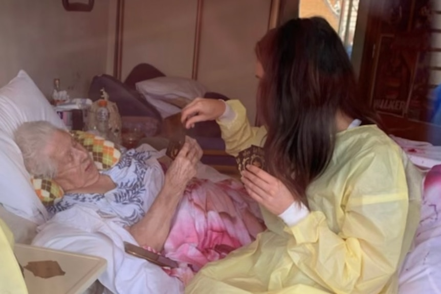 A young woman dressed in PPE plays card with an elderly lady who is laying in a hospital bed