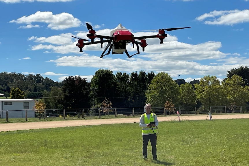 A drone in the air with a man in a yellow jacket standing in the background controlling it using a tablet.