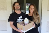 A man and a woman hold a box full of dairy products in front of an open door