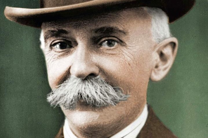 A colourised picture of a bushy- moustached man wearing a jacket, tie and homburg hat.