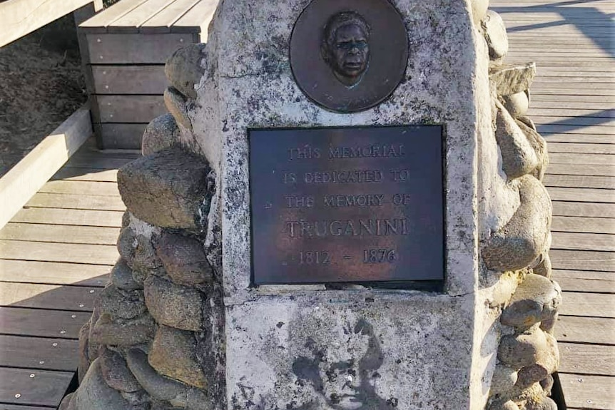 A memorial cairn with plaque of Truganini with Captain Cook stencil.
