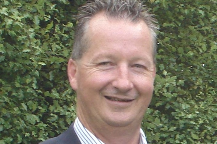 An older man wearing a business shirt and jacket, poses for a formal photo.