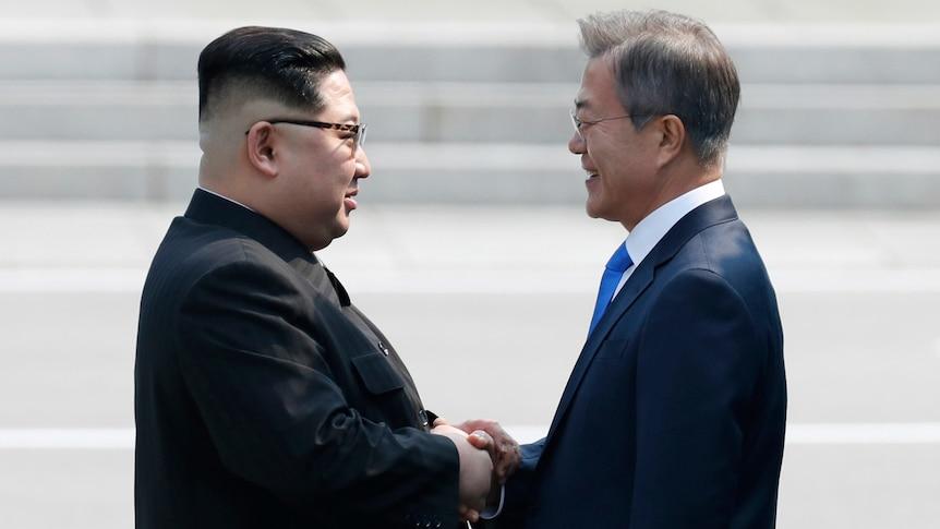 Kim Jong-un shakes hands with Moon Jae-in.