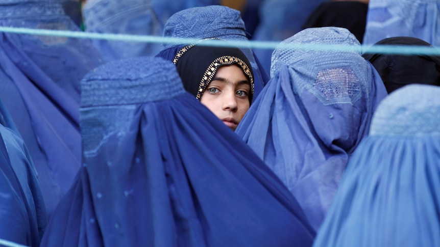 A girl looks on amongAfghanwomen completely covered by blue burqas.