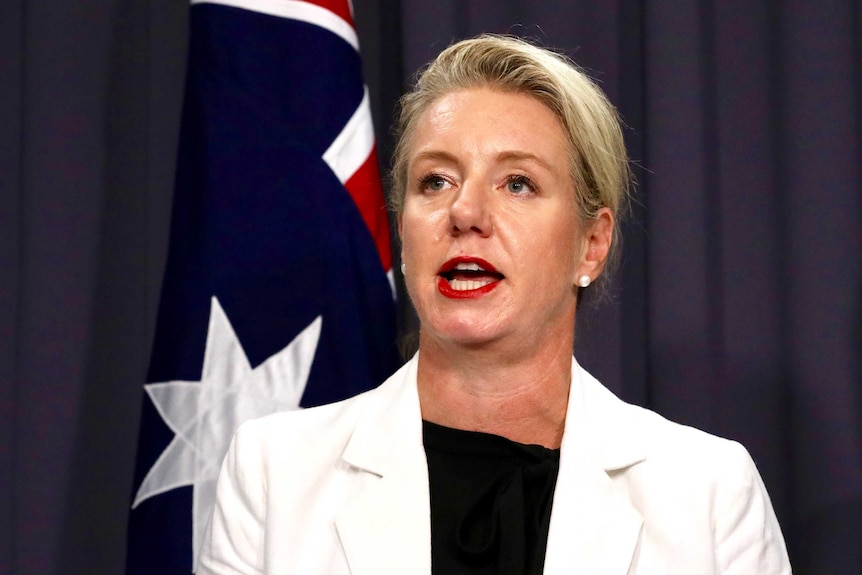 Senator McKenzie is mid sentence, wearing a white blazer and has her hair pulled back.