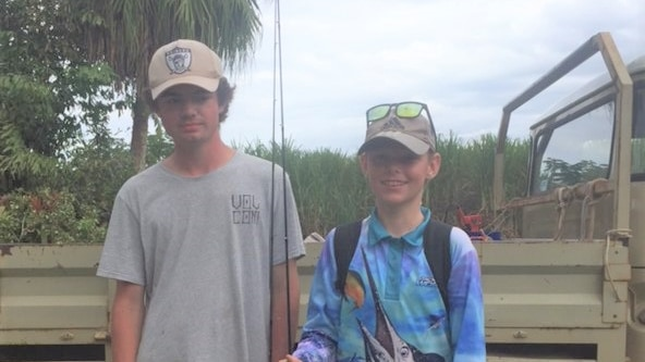 Two boys in fishing outfits stand in front of a ute with fishing rods.
