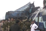 India'ssecurity forces personnel gather at the site of a train accident near Pukhrayan, a train is shown mangled and derailed