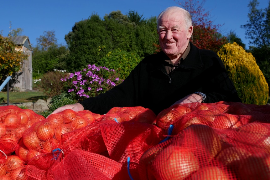 Photo of an old man standing behind a truck full of onions
